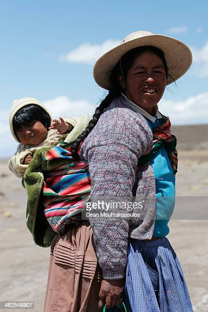 A local mother and child are pictured during Day 9 of the 2014 Dakar Rally near the Salar de Uyuni or Uyuni Salt Flats on January 13 2014 in Uyuni...