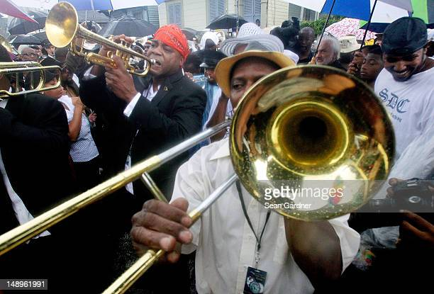 Local musicians play parade down the street during a jazz funeral held for local bass drummer Uncle Lionel Batiste July 20 2012 in New Orleans...
