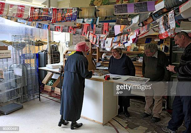 A local news agent dries newspapers and magazines after flood waters destroy her shop in Bandon Ireland outside Cork on November 22 2009 Water...