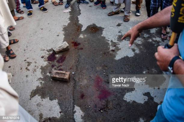 A local news reporter points towards blood stains as people gather around the spot after a grenade attack by suspected militants in a busy market on...