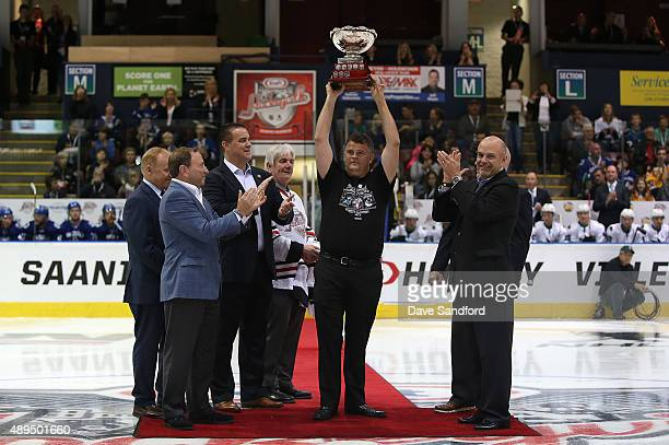 Local Organizing Committee member Jason Fletcher hoists the Kraft Hockeyville trophy prior to the San Jose Sharks taking on the Vancouver Canucks...