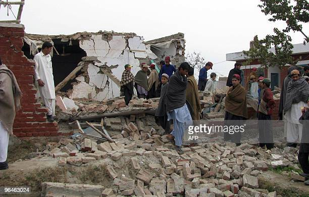 Local Pakistani residents gather over the rubble of a destroyed classroom after militants blew up a girls' school in the village of Huwaid eight...