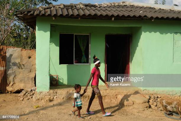 A local Palenquero girl walks her little sister outside a typical color walled house on January 28 2017 in San Basilio de Palenque Colombia Centuries...