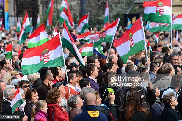 Local participants hold their national tricolor as the Hungarian Prime Minister delivers a speech in front of the National Museum of Budapest on...