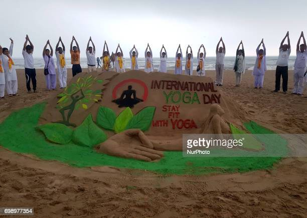 Local people amp visitors look near a sand sculpture creating by sand artist Manas Sahoo for public awareness at the Bay of Bengal Sea's eastern...