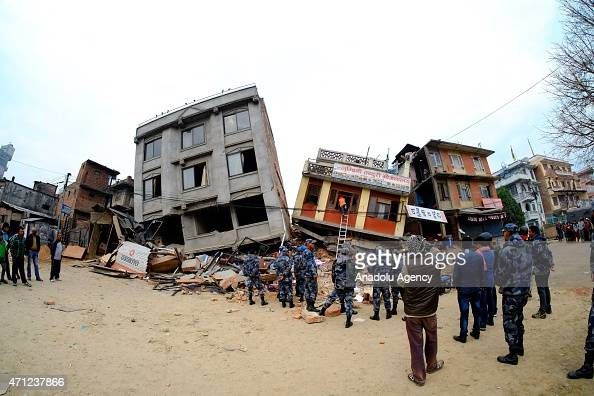 Local people and soldiers inspect debris of destroyed buildings after a powerful earthquake hits Katmandu Nepal on April 26 2015 The death toll in...