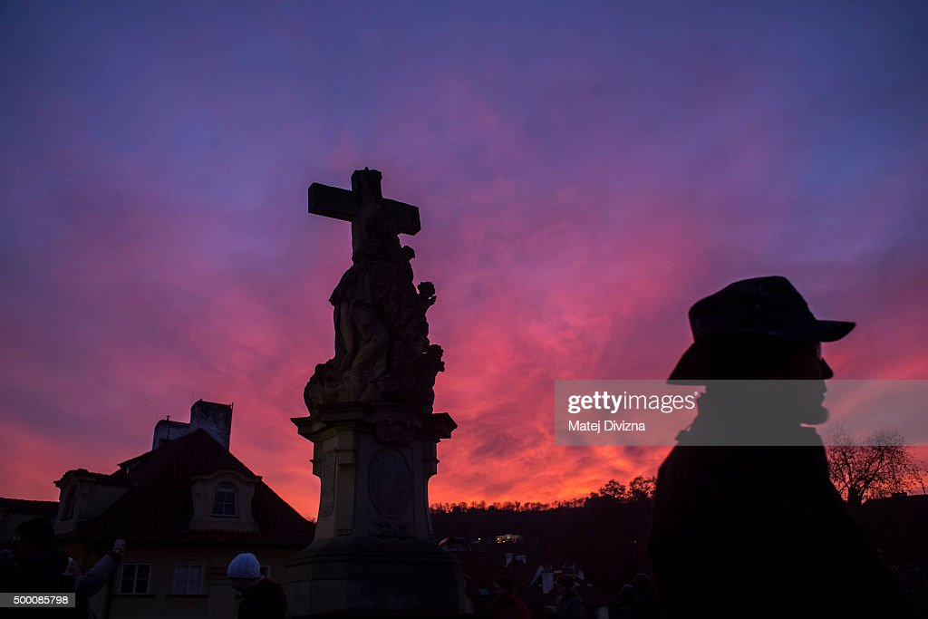 Local people and tourists walk under the statue on the Charles Bridge during the sunset on December 5, 2015 in Prague, Czech Republic.