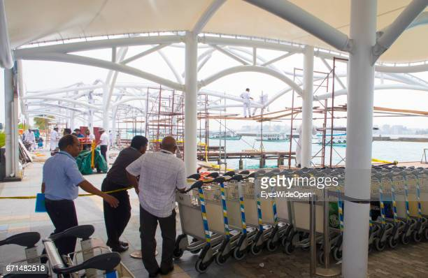 Local people are waiting at Malé International Airport with trolleys watching a construction worker on February 20 2017 in Male Maldives