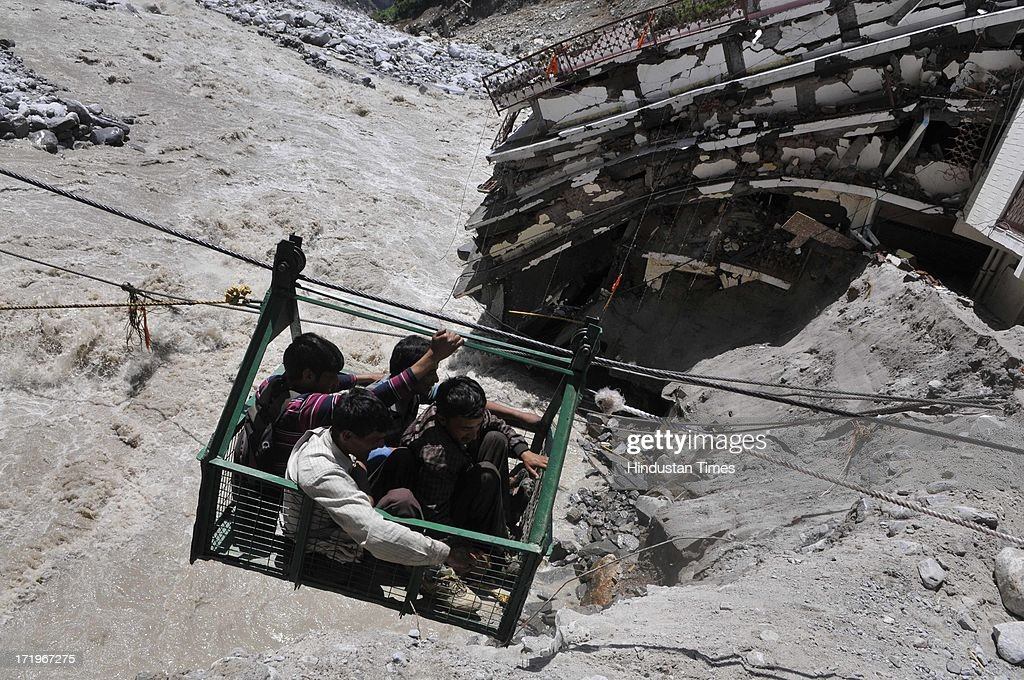 Local people crossing the river Alaknanda in a rope way as the bridge connecting Govind Ghat with the road to Hemkund Sahib Gurudwara is washed away in flash flood at Govind Ghat on June 30 2013 in Uttarakhand, India.