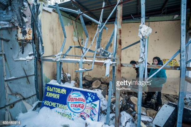 Local people cut wood for heating inside a destroyed market by shelling in Kuibyshevskyi district Donetsk on 15 February 2017