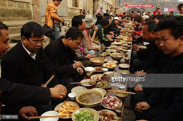Local people entertain visitors with a variety of dishes of food laid out on a long dining table in a street on November 11 2007 in Leishan county...