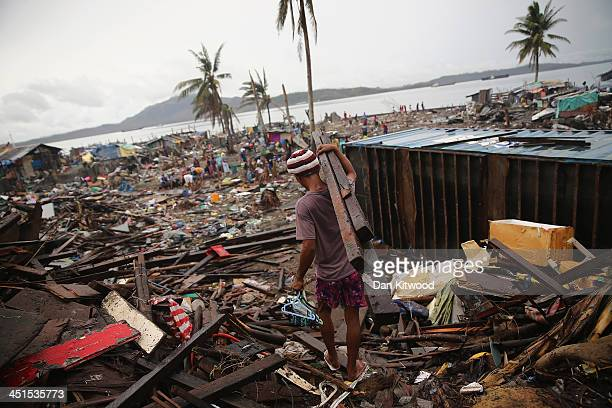 Local people help clear debris near the shoreline where several tankers ran aground in Tacloban on November 23 2013 in Leyte Philippines Bodies...