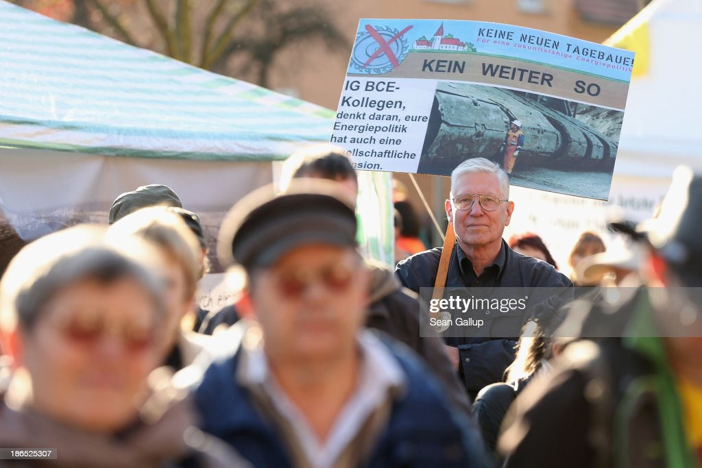 Local people, including one holding a sign that reads: 'No new open-pit mines!', attend a protest against the expansion of open-pit lignite coal mines at the annual village fest on October 31, 2013 in Atterwasch, Germany. According to plans by Swedish energy conglomerate Vattenfall and approved by the Brandenburg state legislature, Atterwasch and at least four other communities are to be raized and their inhabitants compensated and relocated in order to make way for the expansion of the mines. Energy policy and the role of coal is a heated topic at the moment in coalition negotiations between the Social Democrats (SPD) and Christian Democrats (CDU) currently taking place in Berlin.