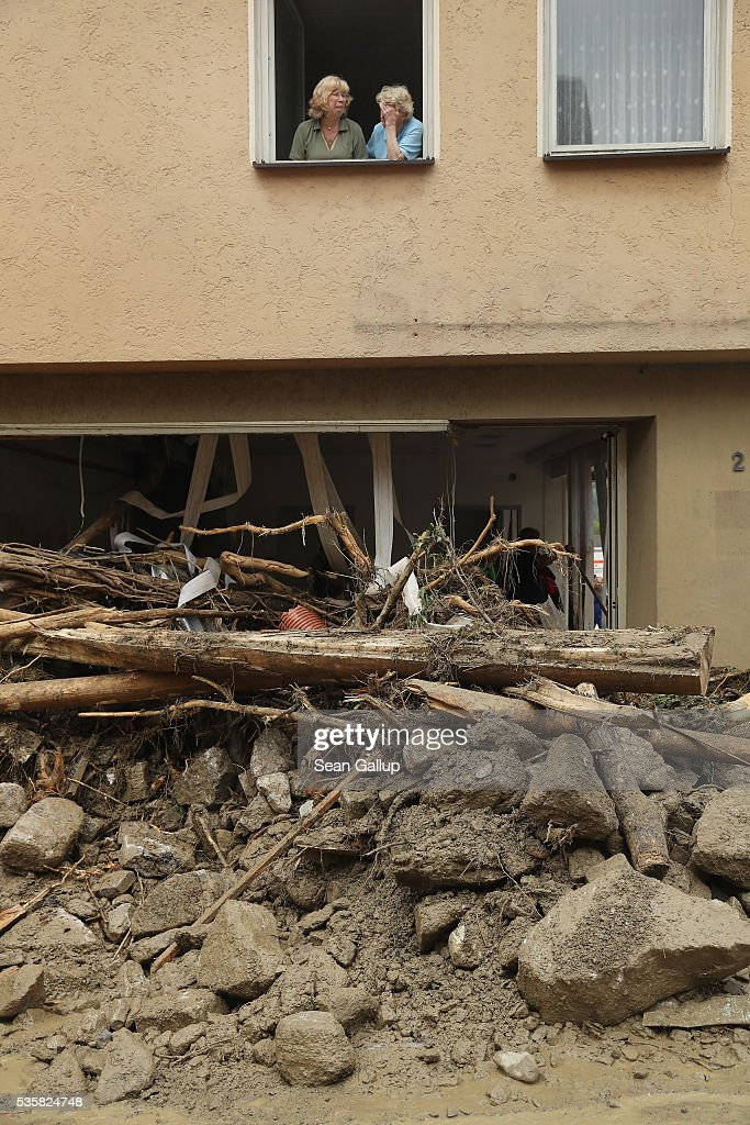 Local people look froma window at boulders and trees lying in the village center following a furious flash flood the night before on May 30, 2016 in Braunsbach, Germany. The flood tore through Braunsbach, crushing cars, ripping corners of houses and flooding homes during a storm that hit southwestern Germany. Miraculously no one in Braunsbach was killed, though three people died as a result of the storm in other parts of the country.
