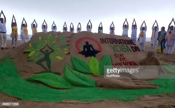 Local people look near a sand sculpture creating by sand artist Manas Sahoo as they are practicing Yoga at the Bay of Bengal Sea's eastern coast...