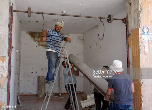 Local people repair a damaged house in Daraa Syria on July 27 2017 Syrians started to return their homes after Assad regime forces stopped attacking...