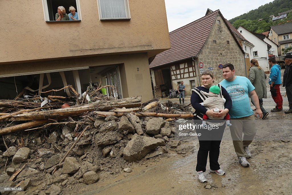 Local people stand among boulders, smashed trees and other debris in the village center following a furious flash flood the night before on May 30, 2016 in Braunsbach, Germany. The flood tore through Braunsbach, crushing cars, ripping corners of houses and flooding homes during a storm that hit southwestern Germany. Miraculously no one in Braunsbach was killed, though three people died as a result of the storm in other parts of the country.