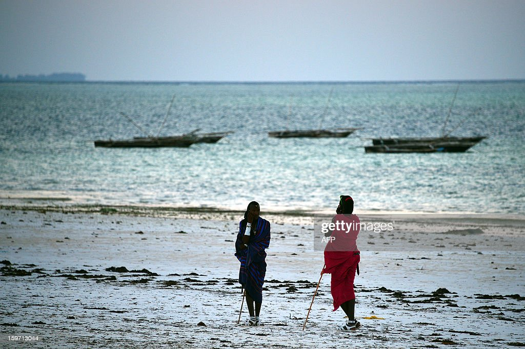 Local people stand on a beach on January 6, 2013 in Zanzibar. AFP PHOTO / GABRIEL BOUYS
