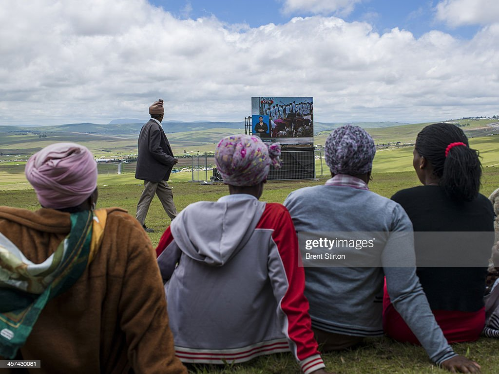 Local people watches the Mandela funeral service on a large television situated on a hilltop overlooking the service in the valley below, Qunu, South Africa, 14 December 2014. An icon of democracy, Mandela was buried at his family home in Qunu after passing away on the 5th December 2013.