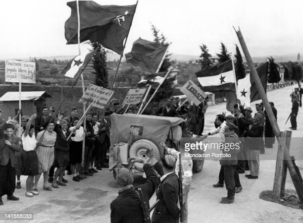 Local people waving flags and signs to a British jeep directed to Trieste passing by Pieris San Canzian d'Isonzo May 1945