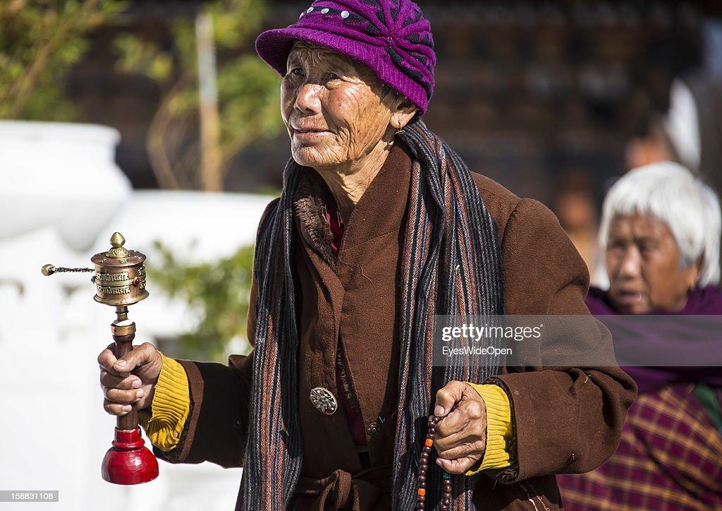 Local people with prayer wheels and tourists circumambulate Bhutan's Choeten Memorial, built in memory of the late third King Jigme Dorji Wangchuk on November 18, 2012 in Thimphu, Bhutan.