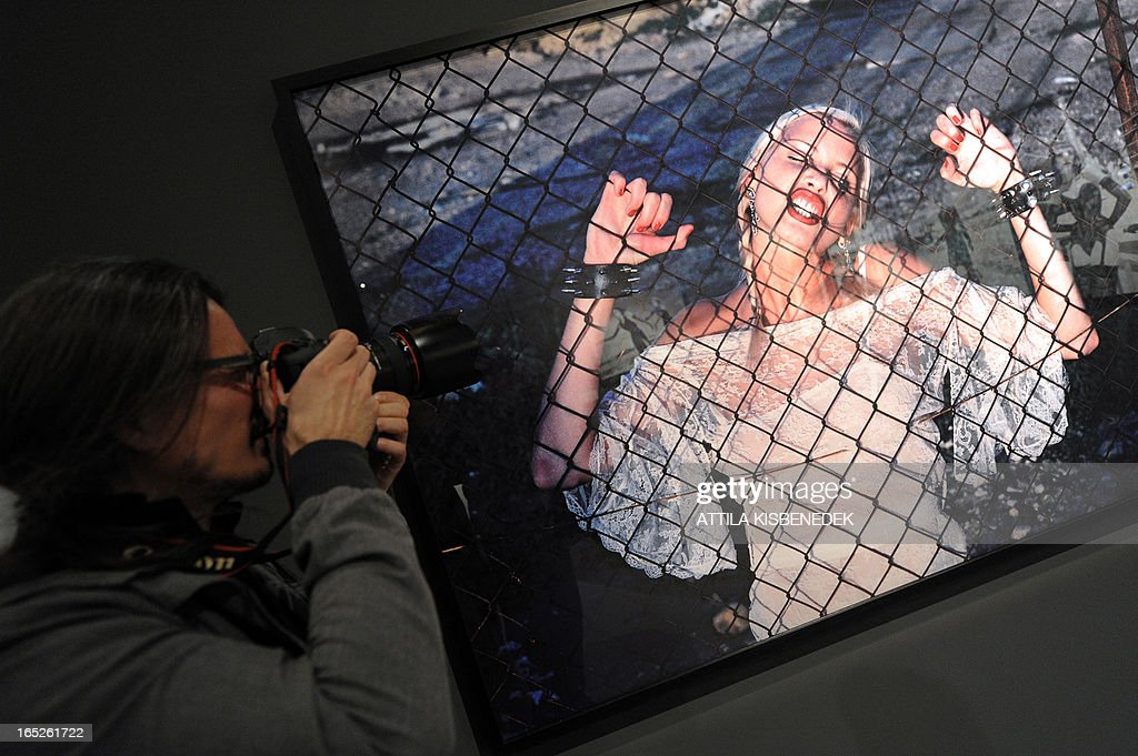 A local photographer takes his picture in front of a photo by the German born photographer Helmut Newton (Neustadter) (1920-2004) in the Museum of Fine Arts of Budapest on April 2, 2013 during a presentation of Newton's photographic exhibition for press. The show features around 250 shots by one of the greatest figures of fashion and advertising photography Newton, reflecting his most significant creative periods. The material will be assembled with the cooperation of the Helmut Newton Stiftung, the foundation taking care of the artist's oeuvre in Berlin. The photographic exhibition will be opened on April 3. AFP PHOTO / ATTILA KISBENEDEK CREDIT 'AFP PHOTO / ATTILA KISBENEDEK ' - NO