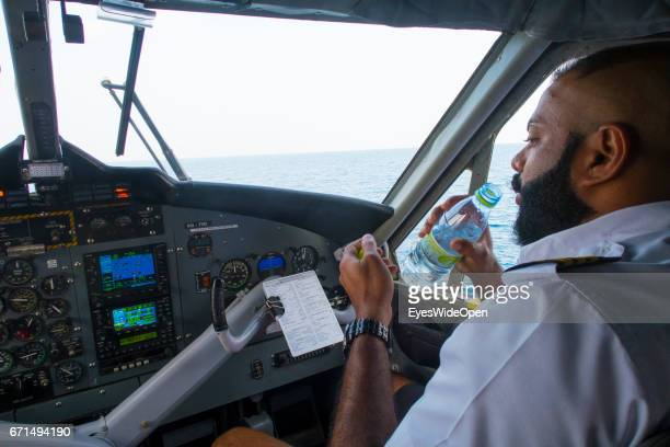 Local Pilot in the Cockpit is flying a Seaplane of Trans Maldivian Airways and drinking Water on February 23 2017 in Male Maldives