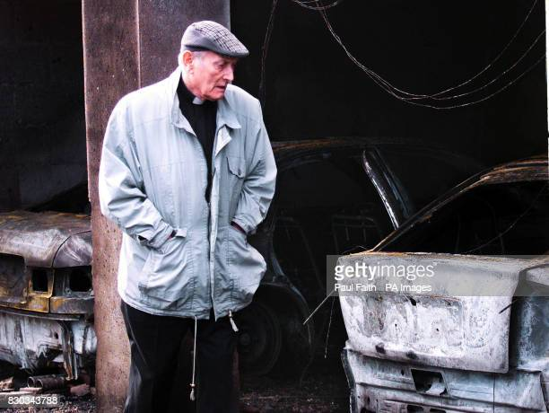 A local priest looks at the burntout shell of one of four priests' cars which were destroyed in Dungannon County Tyrone The blaze was adjacent to the...