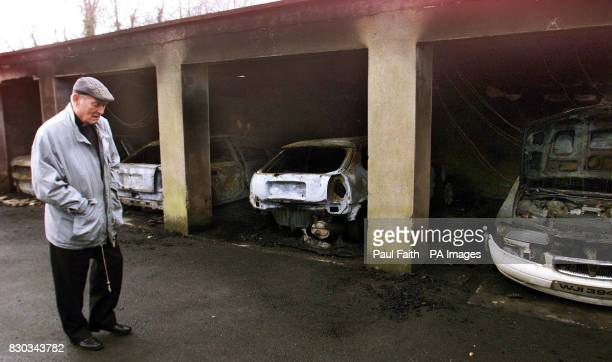 A local priest walks in front of the burntout shells of four priests' cars which were destroyed in Dungannon County Tyrone The blaze was adjacent to...
