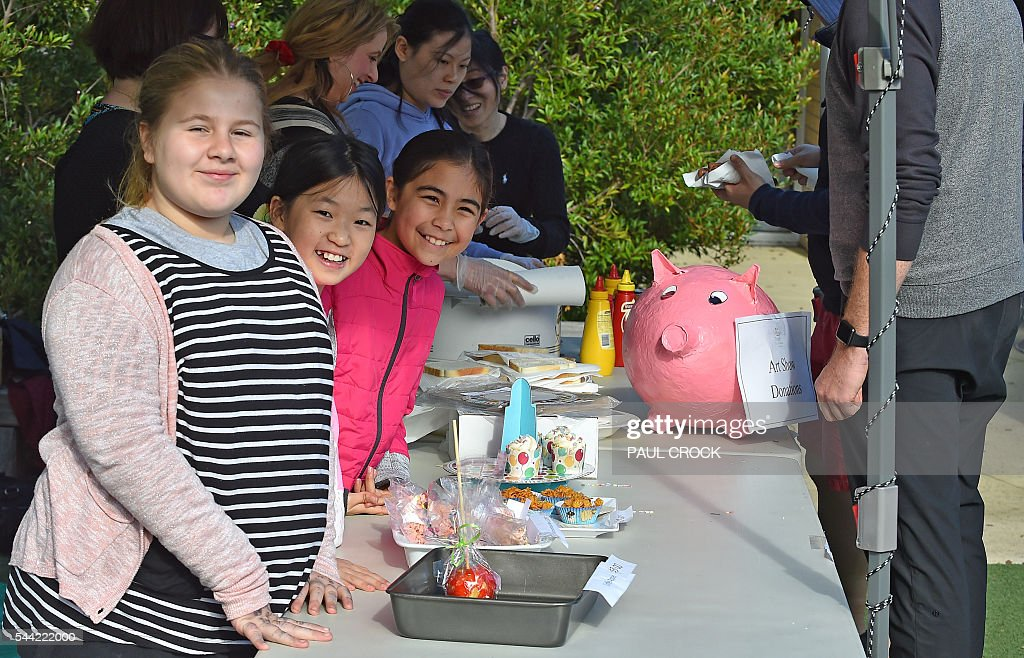 Local primary school children in the inner city suburb of Richmond happily sell cakes, lollies and sausages to people as they wait in line to cast their vote in the Australian Federal Election in Melbourne on July 2, 2016. Australia is voting in a general election which is expected to be a close race between the ruling Liberal-National coalition and the opposition Labor Party. / AFP / Paul Crock