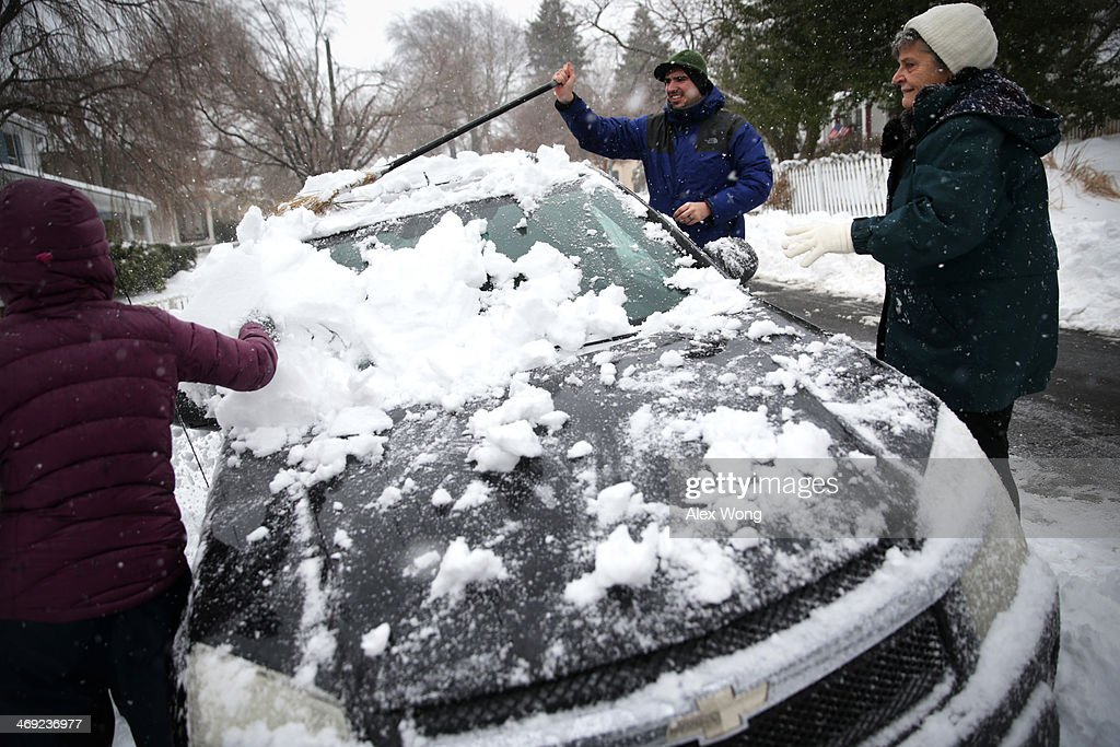 Local resident Andrew Gordon (2nd R) helps to clean up snow on his neighbor Claire Lamborne's (R) car February 13, 2014 in Warrenton, Virginia. The Washington, DC, area is embracing the biggest sown storm in four years. Most of the metropolitan area has received almost a foot of snow so far.