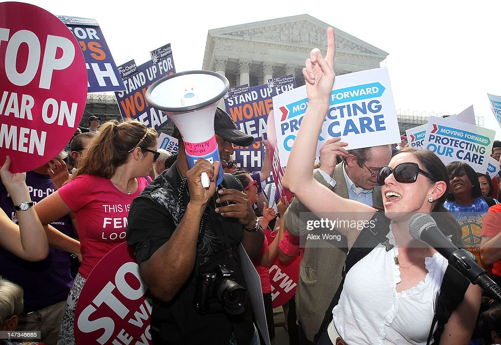 Local resident Angela Botlicella (R), along with other Obamacare supporters, celebrate as they respond to the Supreme Court ruling on the Affordable Health Act June 28, 2012 in front of the U.S. Supreme Court in Washington, DC. The Supreme Court has upheld the whole healthcare law of the Obama Administration.