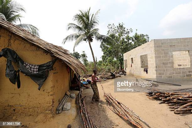 A local resident arranges wood purchased for the construction of a new house funded with compensation money paid to the people of Bodo community by...