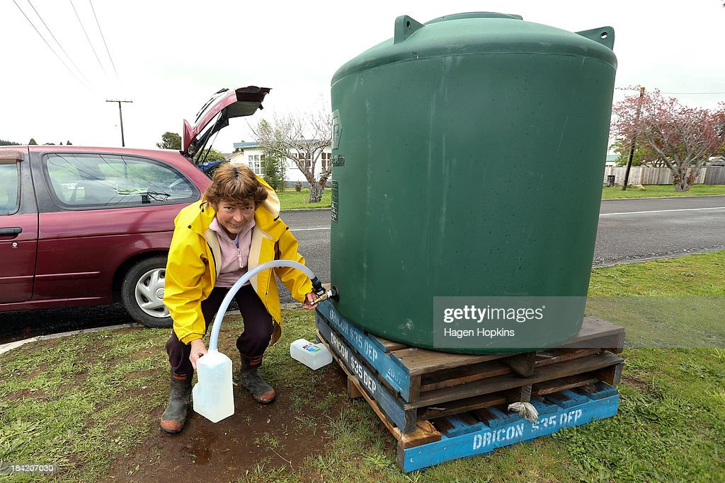 Local resident Bev Mott fills a water container from a street-side water tank on October 12, 2013 in Raetihi, New Zealand. Work has begun to flush a stream contaminated by a large diesel spill at Tongariro National Park. A tank from the Turoa Ski Field has leaked 15,000 litres of diesel into the Makotuku stream.
