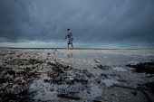 Local resident Bob Barchie takes a walk along the shore in front of the TradeWinds Hotel in St Pete Beach Florida after the remnants of Tropical...