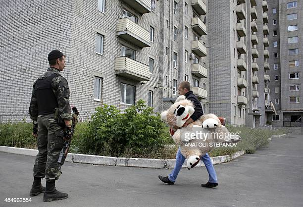 A local resident carries a toy bear as a Ukrainian serviceman patrol on September 8 2014 near a residential building damaged during recent shelling...
