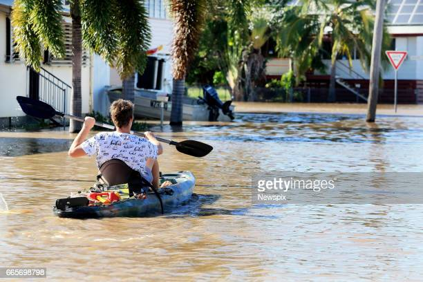 ROCKHAMPTON QLD Local resident Chris O'Beirne paddles his canoe through floodwaters at Depot Hill in Rockhampton Queensland after the Fitzroy River...