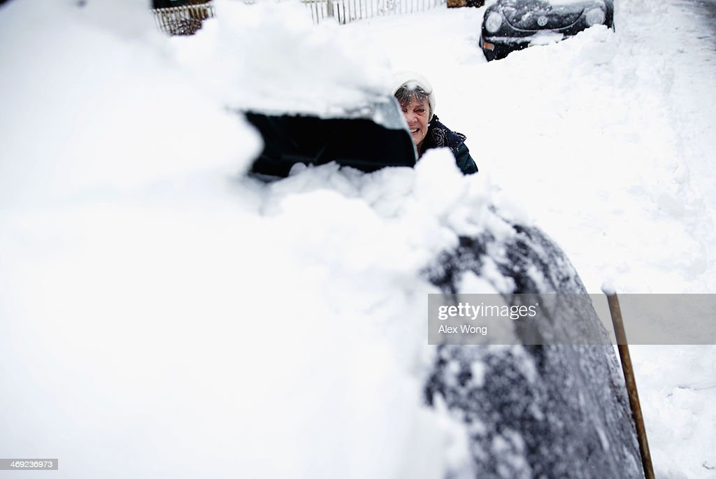 Local resident Claire Lamborne removes snow on top of her car February 13, 2014 in Warrenton, Virginia. The Washington, DC, area is embracing the biggest sown storm in four years. Most of the metropolitan area has received almost a foot of snow so far.
