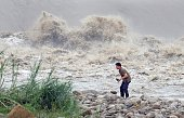A local resident collects stones from the Xindian river after Typhoon Dujuan passed in the New Taipei City on September 29 2015 Super typhoon Dujuan...