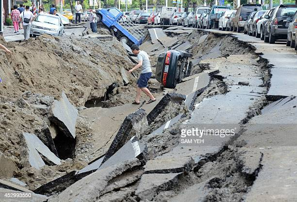 A local resident crosses the gas explosion site in the southern Taiwan city of Kaohsiung on August 1 2014 A series of powerful gas blasts killed at...