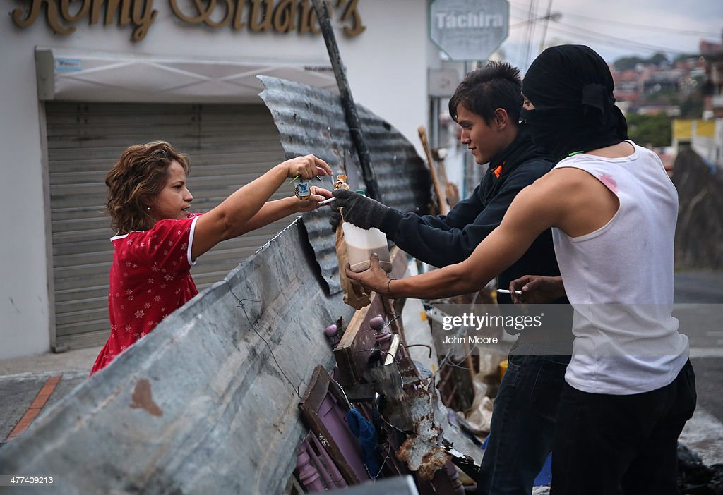 A local resident delivers bread and coffee to student protesters at dawn on March 9, 2014 in San Cristobal, the capital of Tachira state, Venezuela. Local residents and students have manned barricades throughout the nights, skirmishing with security forces for almost a month, while protesting against the federal government. Tachira, which borders Colombia, has been a focal point for anti-government protests nationwide.