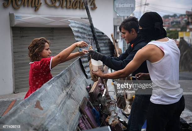A local resident delivers bread and coffee to student protesters at dawn on March 9 2014 in San Cristobal the capital of Tachira state Venezuela...