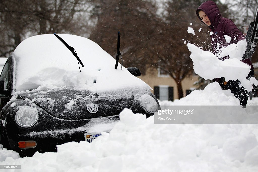 Local resident Grace Gordon digs her car out of snow February 13, 2014 in Warrenton, Virginia. The Washington, DC, area is embracing the biggest sown storm in four years. Most of the metropolitan area has received almost a foot of snow so far.