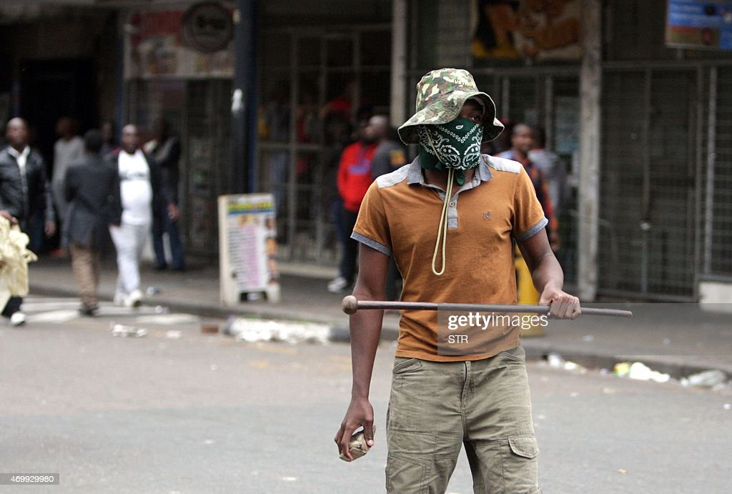 A local resident holds a stone and a traditonal Zulu weapon after a skirmish with foreigners as thousands of people take part in the 'peace march'...