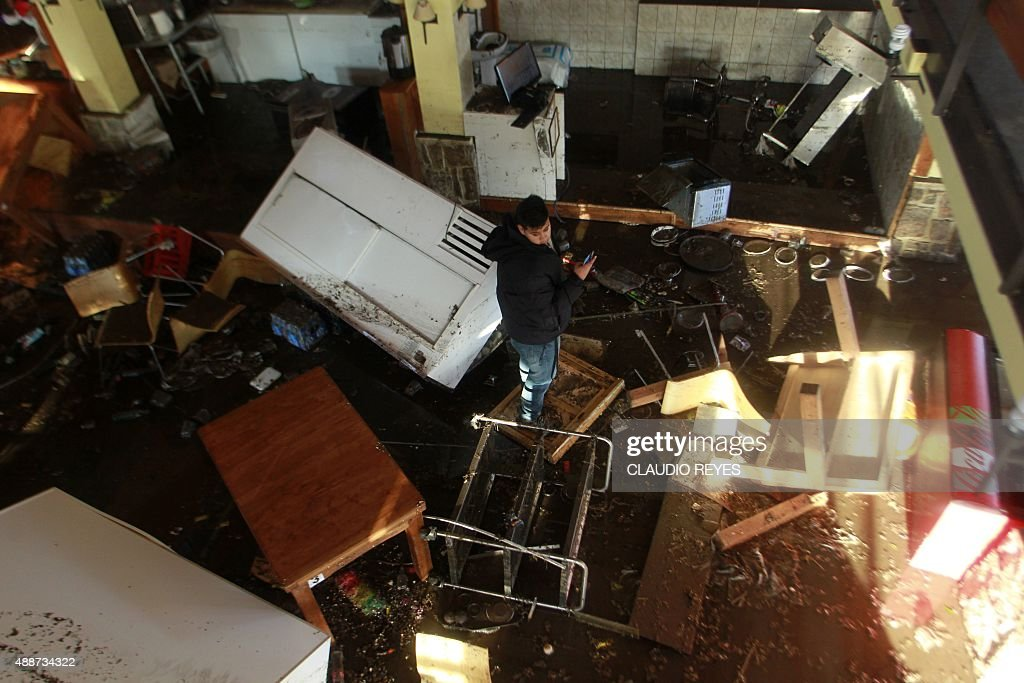 A local resident inspects the damage in his home in Concon some 110 km northwest of Santiago on September 17 2015 hit by an earthquake on the eve A...