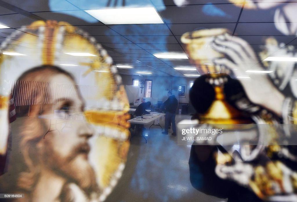 A local resident is reflected on a religious picture as he votes for the first US presidential primary at a church in Concord, New Hampshire, on February 9, 2016. New Hampshire voters headed to polls at the snowy break of day on February 9 for the crucial first US presidential primary, with Donald Trump chasing victory and Hillary Clinton looking to narrow the gap on Bernie Sanders. The northeastern state, home to just 1.3 million people, sets the tone for the primaries -- and could shake out a crowded Republican field as the arch-conservative Senator Ted Cruz and establishment candidates led by Marco Rubio battle for second place behind the frontrunner Trump. / AFP / Jewel Samad