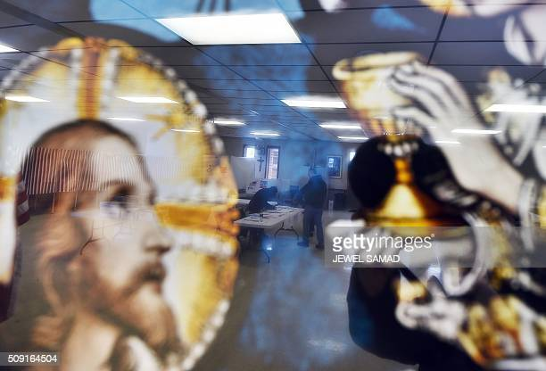 A local resident is reflected on a religious picture as he votes for the first US presidential primary at a church in Concord New Hampshire on...