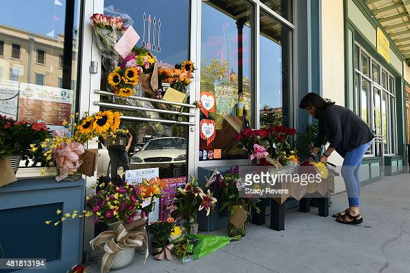 A local resident leaves flowers at a makeshift memorial outside of a store owned by one of the victims Jillian Johnson on July 24 2015 in Lafayette...