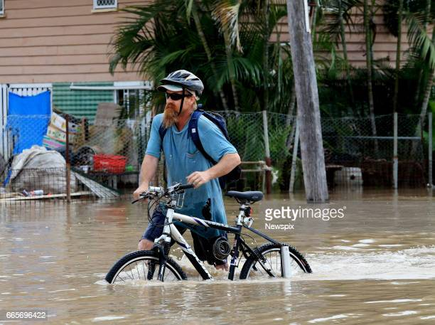 ROCKHAMPTON QLD Local resident Leonard Peckhaus pushes his bicycle through floodwaters at Depot Hill in Rockhampton Queensland after the Fitzroy...