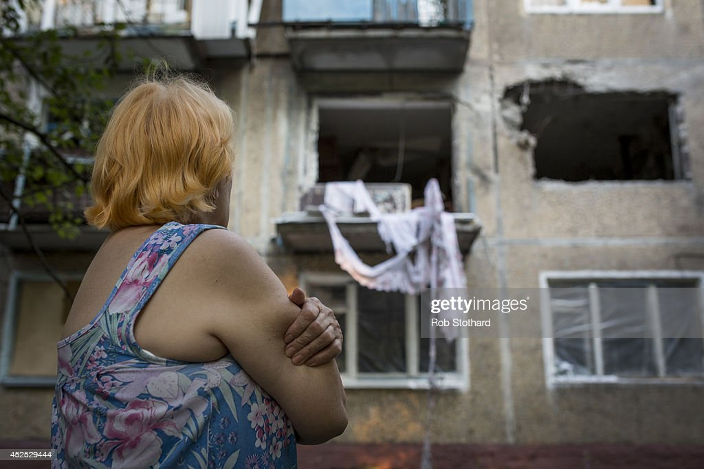 A local resident looks at an apartment building damaged by rocket fire on July 22 2014 in Donetsk Ukraine Ukrainian government troops clashed again...